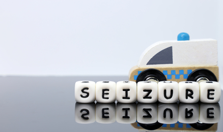 image of letters spelling a word seizure and a model ambulance on a reflecting background Reklamní fotografie