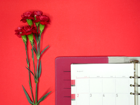 calandar: a top view image of a calendarorganizer on a bright red paper background