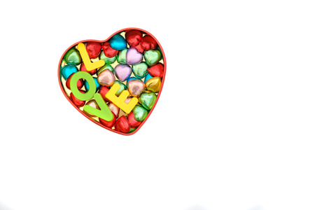 heart-shaped chocolate candies in various colors in a heart-shape tin box together with letters spelling LOVE, Valentines Day, romantic concept, top view, isolated on white, with copy space