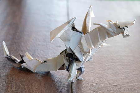 A Model Origami Dragon Made From Creamy Heavyweight Magazine Paper On Wooden Table Top
