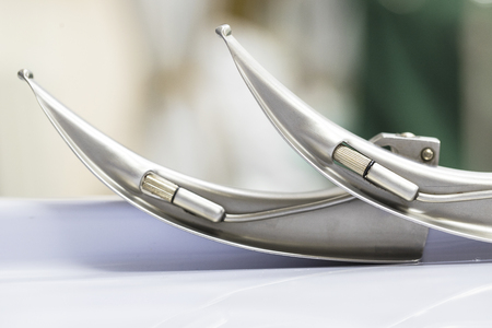 two shiny metal laryngoscope blades on a metal table top
