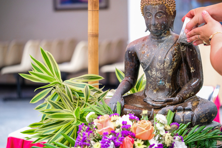 Thai people make merit on Songkran Day by offering scented water and flowers on Buddha Statue