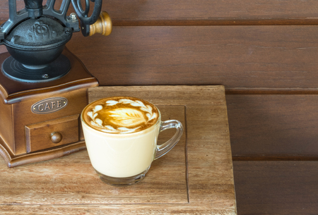 a cup of warm coffee latte on a small wooden table in a cozy room