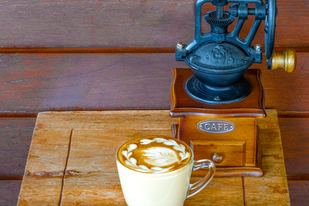 a cup of warm latte on a small wooden table with a vintage coffee grinder