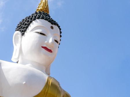 A huge white painted buddha statue is on public display outdoor, This iconic figure is in Chiang Mai City, Thailand. Isolated sky background