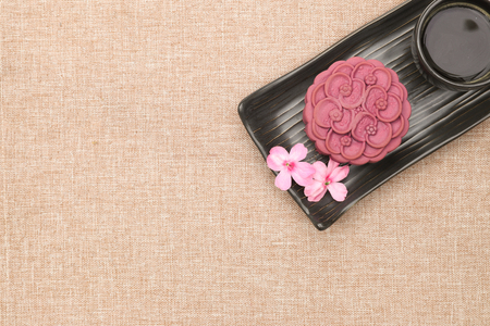 A non-traditional chinese moon cake made of purple japanese yam on a black ceramic plate with a cup of espresso.  Top view, light brown linen background.