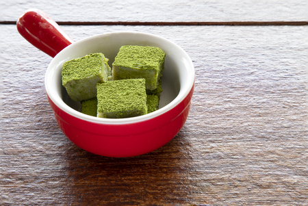 White chocolate fudge cubes heavily coated with fine green tea powder in a red ceramic dish Imagens