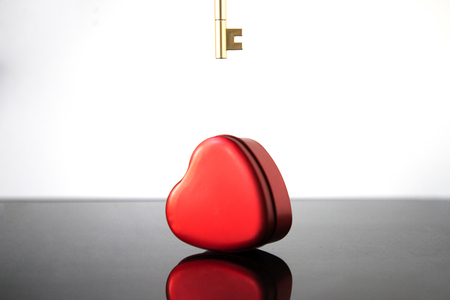 A crimson heart and a gold key on a blurred black and white Imagens