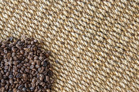 Fresh coffee beans and water hyacinth natural wickerwork background. Closeup top view.