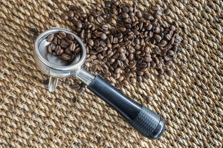 Fresh coffee beans and a coffee maker machines portafilter and filter basket. Water hyacinth natural wickerwork background. Closeup top view.