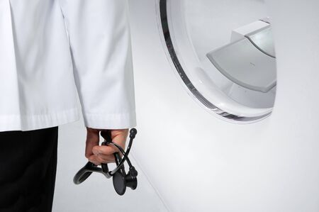A doctor holding a black stethoscope standing in front of a CT scanner.