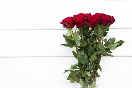 Beautiful blooming bouquet of red roses in a clear glass vase.