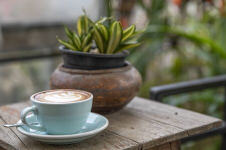 Warm cappuccino coffee in a teal color ceramic cup on a wooden table. Blurred garden background.