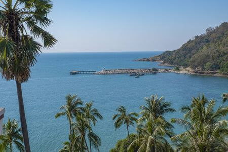 A stony pier in a small harbor with simmering turquoise sea. Green coconut trees swaying  in the gentle breeze. 写真素材
