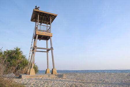 A tall wooden beach guard tower on a white sandy seashore catching golden light of the late afternoon sun. 写真素材