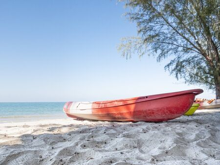 A red kayak on a beach.