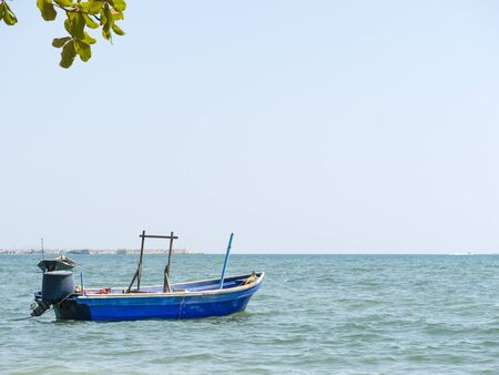 A small traditional wooden blue and green fishing boat anchoring in the calm harbor.