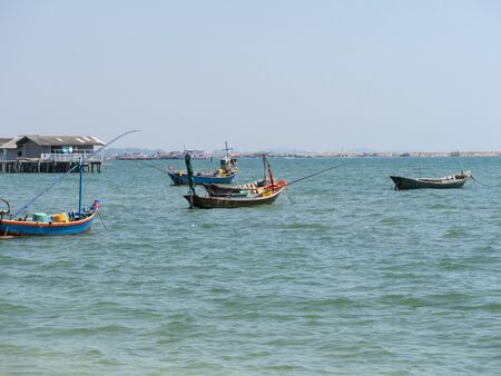 Small traditional wooden blue and green fishing boats anchoring in the shallow harbor.