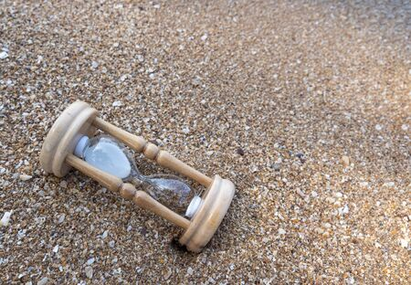 Close up of a broken hourglass filled with fine white granular sand lying on a coarse sandy beach.