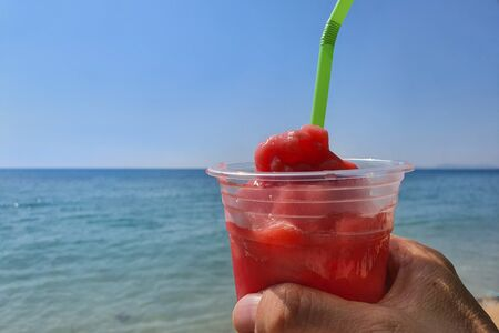 a hand holding watermelon smoothie with blurred sea and sky background.