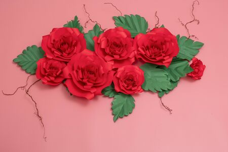 A group of paper roses and dried veins on salmon pink background.