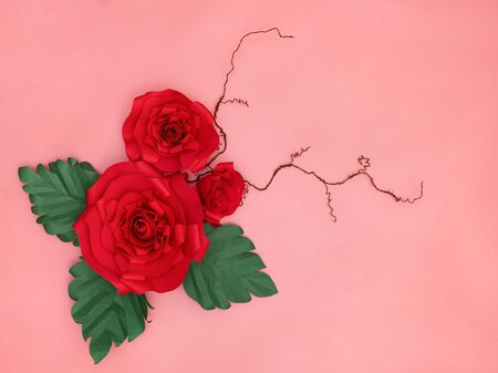 Red paper roses and tiny twigs in salmon pink background.