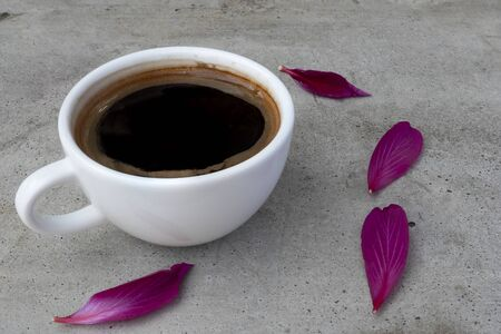 A white ceramic cup of coffee on a grey concrete table  with violet red petals of orchid tree flower. Side view.