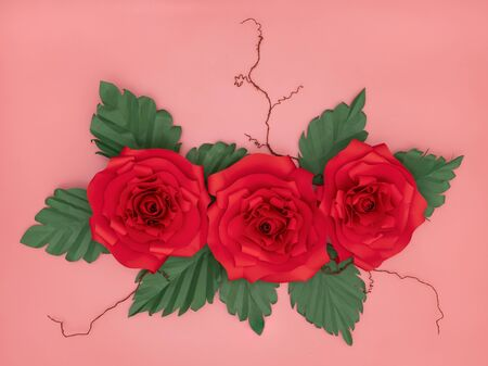 Red paper roses and tiny white flowers with dried veins on salmon pink background.
