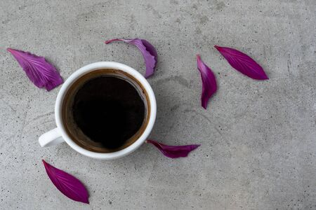 A white ceramic cup of coffee on a grey concrete table  with violet red petals of flower. Top view.
