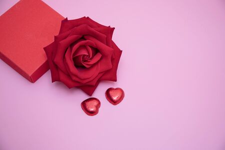 Closeup of a red rose with two chocolate candy hearts and a red gift box on pink background.  Valentines,  anniversary, wedding concept. 写真素材