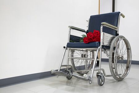 Red roses bouquet on a blue wheelchair.  Hospital or clinic background