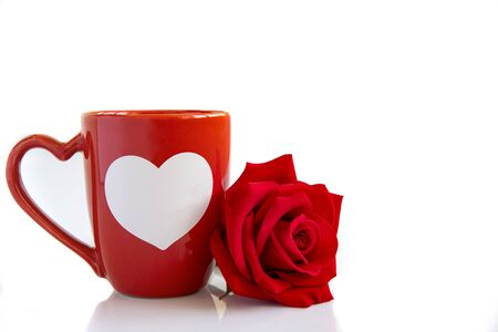 Closeup of an orange coffee mug with a beautiful blooming red rose on white backbround.  Valentines,  anniversary, wedding concept. 写真素材