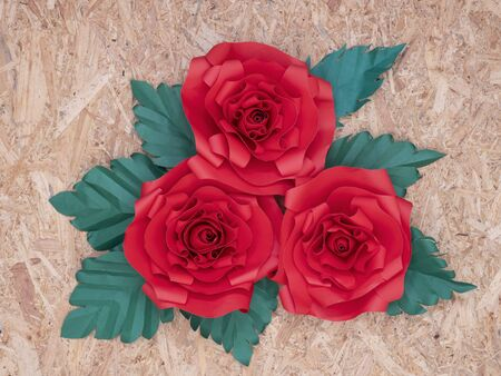 Beautiful hand-crafted paper crimson red roses with green leaves on vintage wooden board background.   写真素材