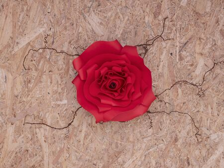 Beautiful hand-crafted paper crismson rose on thorny veins. Wooden board background.