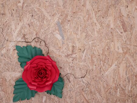 A beautiful hand-crafted paper crimson red rose with thorny veins on vintage wooden board background.