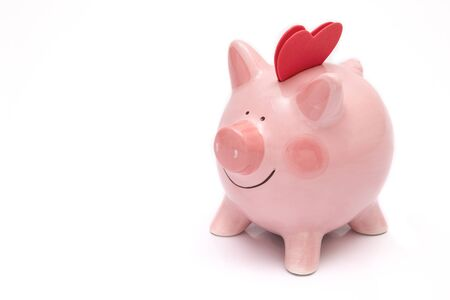 Two red hearts on a piggy bank. Depositing love and happiness concept.