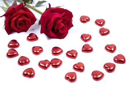 Closeup of beautiful red roses  on red candy hearts.  Valentines,  anniversary, wedding concept.