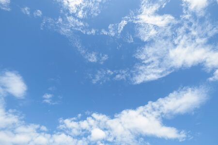 Blue sky with fluffy white clouds background.