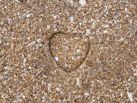A heart impression on a sand at a sandy beach. 写真素材