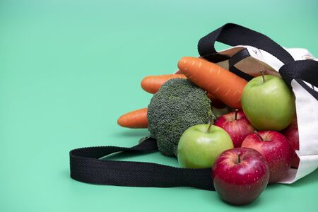 Apples and vegetables in cloth bag .  Cloth bag campaign advertising and healthy living concepts. Green background.