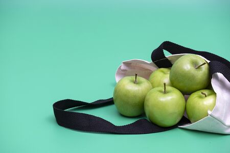 Green apples in natural color cloth bag . Cloth bag campaign advertising and healthy living concepts. Green background.