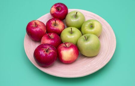 Red and green apples on a bamboo plate. Green background. Healthy eating concepts.