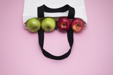 Green and red apples in natural color cloth bag . Cloth bag campaign advertising and healthy living concepts. pink pastel background. 写真素材