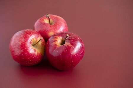Three red gala apples on mahogany background. Closeup macro view. 写真素材