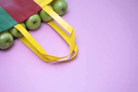 Closeup of green apples in multicolor reused plasti bag.  Recycled bag campaign advertising and healthy living concepts. magenta background.