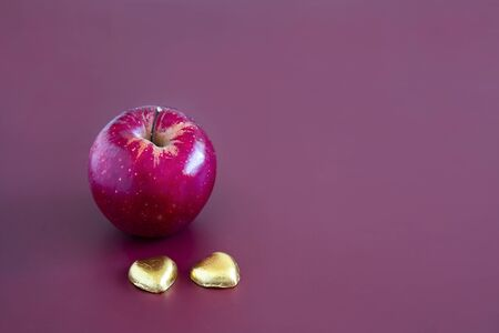 Closeup of a red gala apple with two heart shape chocolate candy. Mahogany background.