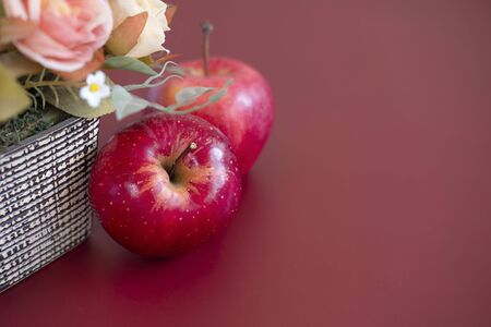 Two red gala apples on mahogany
