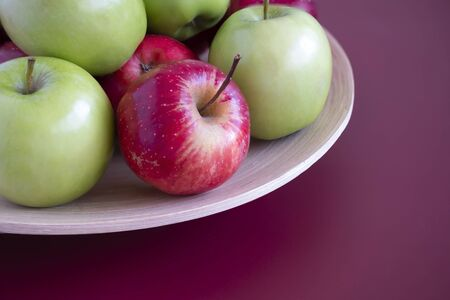 Closeup of red and green apples on a bamboo plate. Mahogany background.