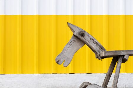 An old wooden pony in front of a white and yellow galvanized steel wall.