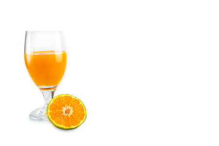 A glass of fresh orange juice with a slice of cut orange fruit placed in front of it. Isolated on white background.